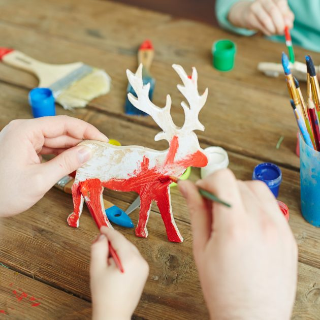 Hands of adult and kid painting wooden deer in red