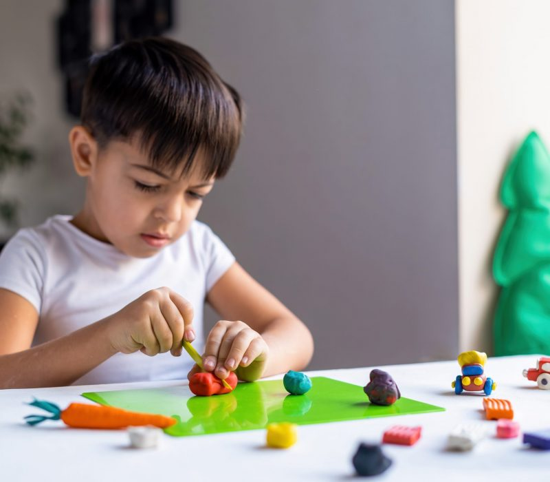 Small caucasian boy playing with colored plasticine and making figures on the white table. Happy child idea